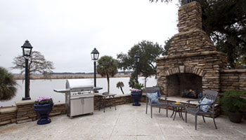 outdoor patio space with gas grill and fire place
