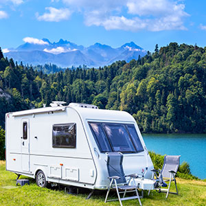 RV Camper Parked by Lake Surrounded by Mountains