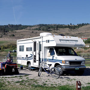 RV Camper Parked with Person Sitting At Picnic Table