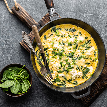 Spinach Fetta Frittata in pan on wood cutting board with side of spinach in small bowl