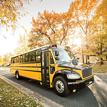 Propane Autogas School Bus Driving on Fall Covered Road
