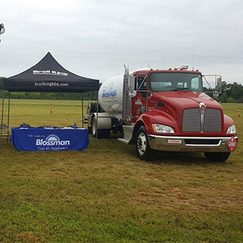 Two Blossman Trucks on either side of a tent for a 'Big Toy Day' in NC