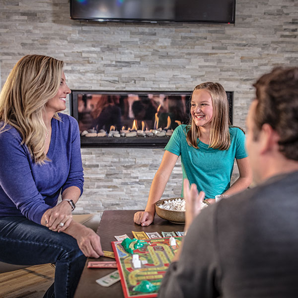 Family playing board game in front of gas fireplace