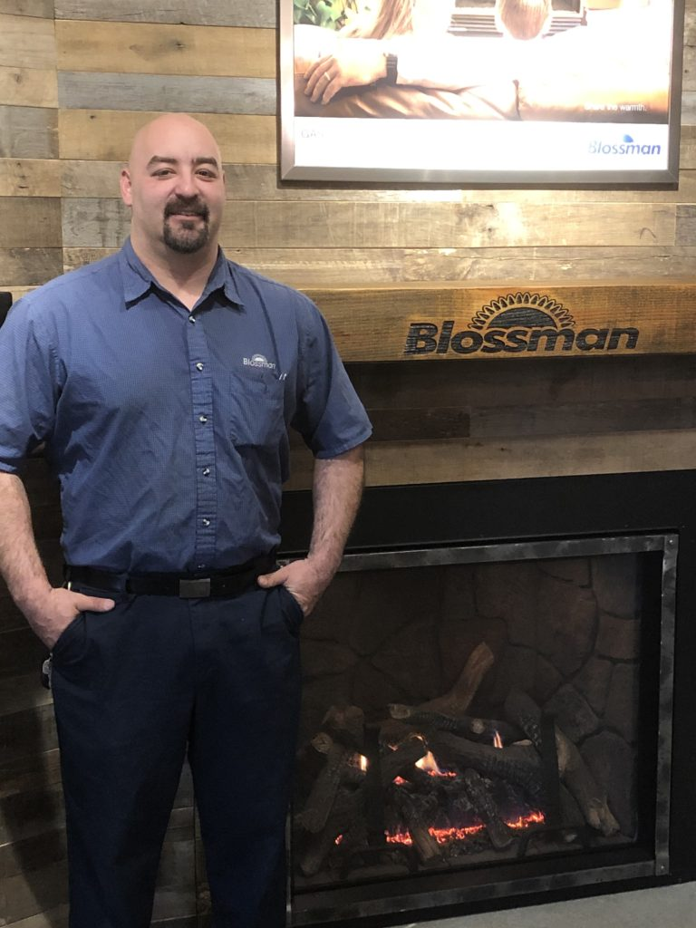 Dennis Smith - Blossman Gas Service Technician Pictured At Blossman Gas Store in Front of Fireplace