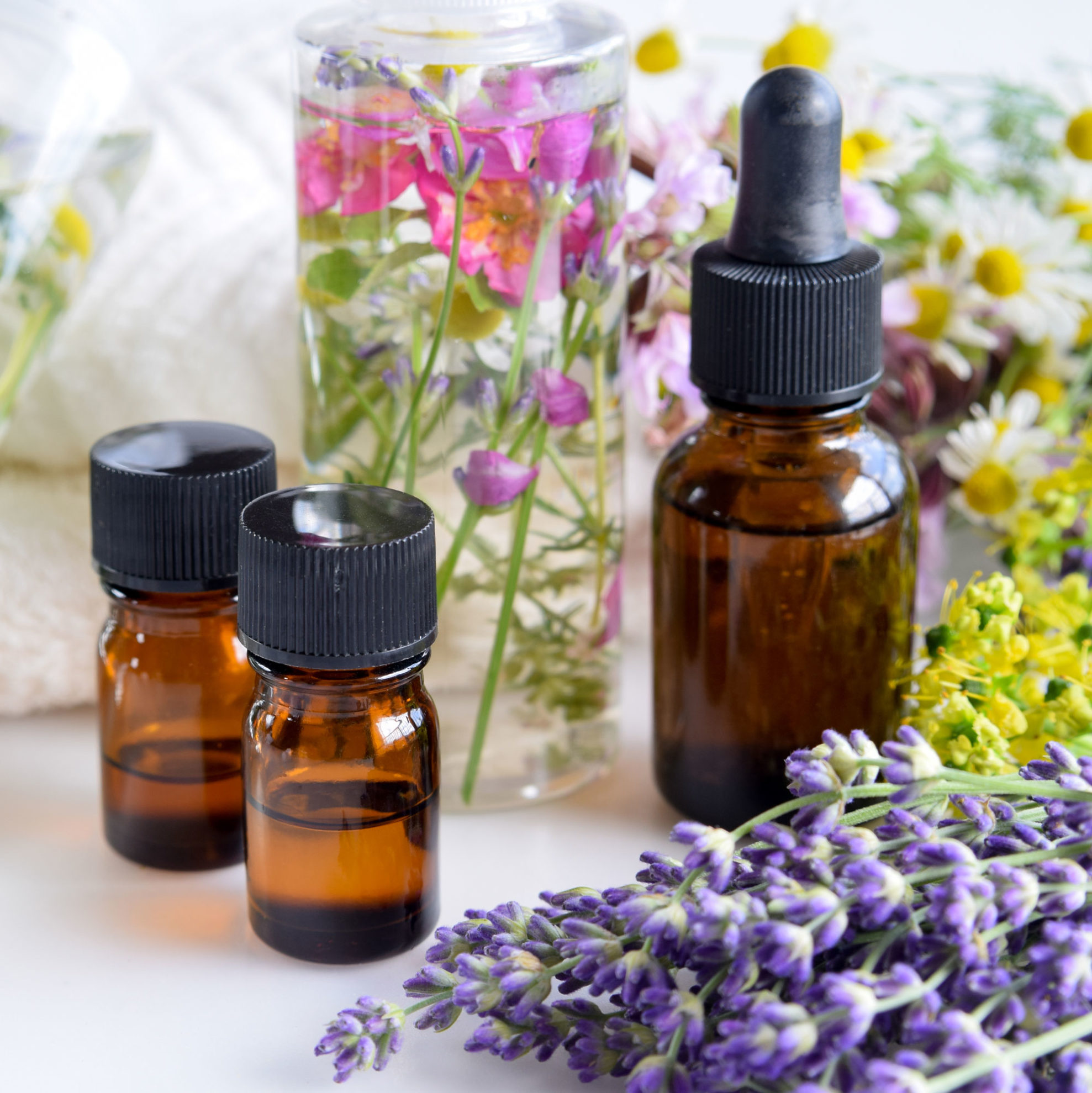 Homeade Aromatherapy Bottles With Various Flowers around Including lilac