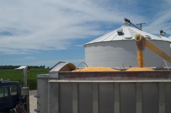 Grain Bin on Farm with Truck Picking Up Grain