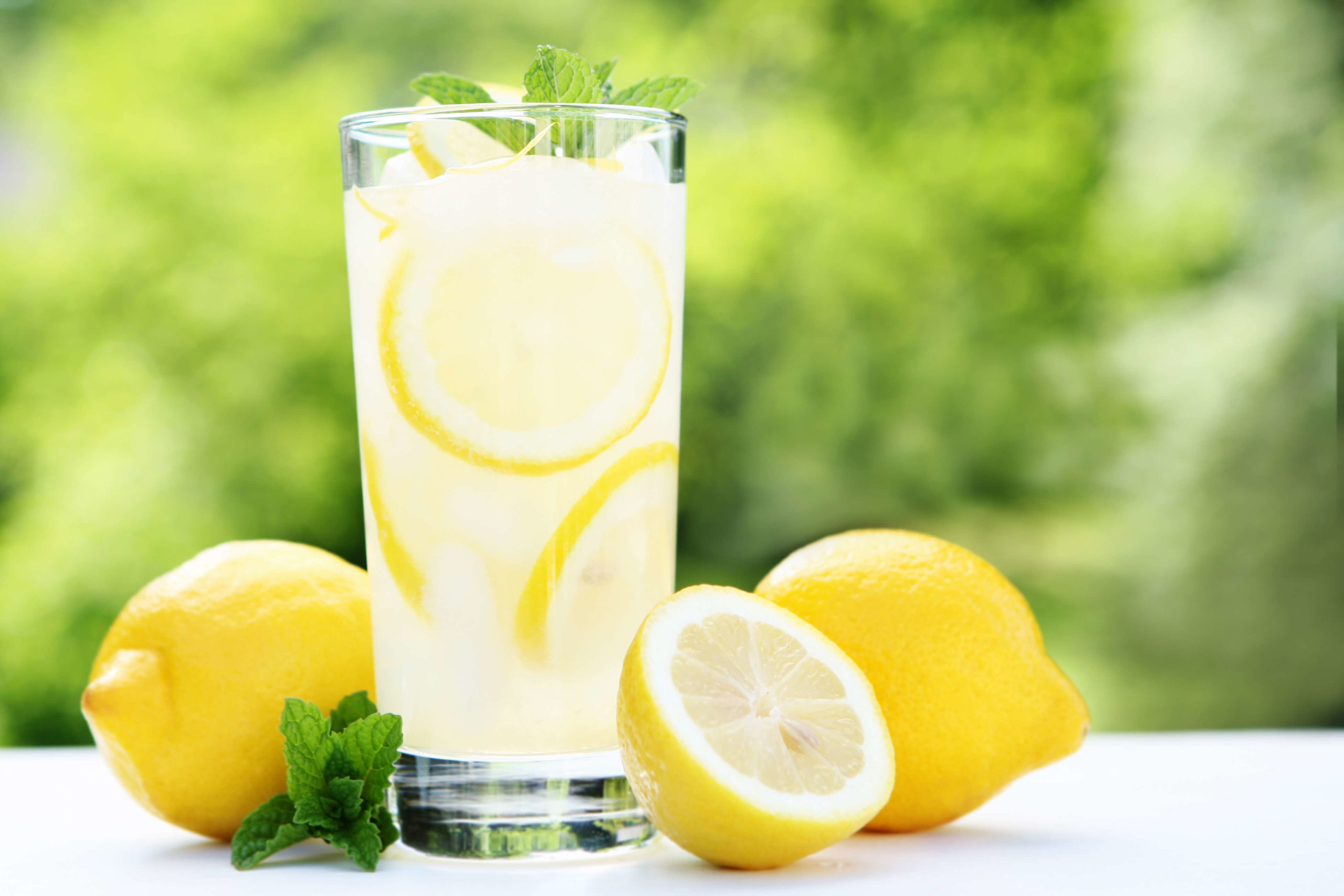 Cup of fresh lemonade with lemons on table and mint garnish in glass