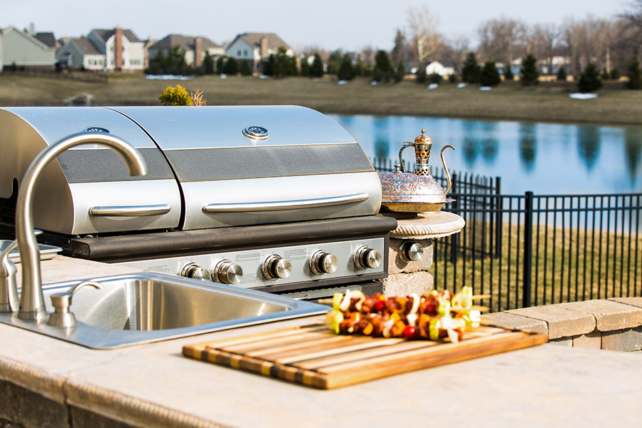 Grill and outdoor sink overlooking gated lake