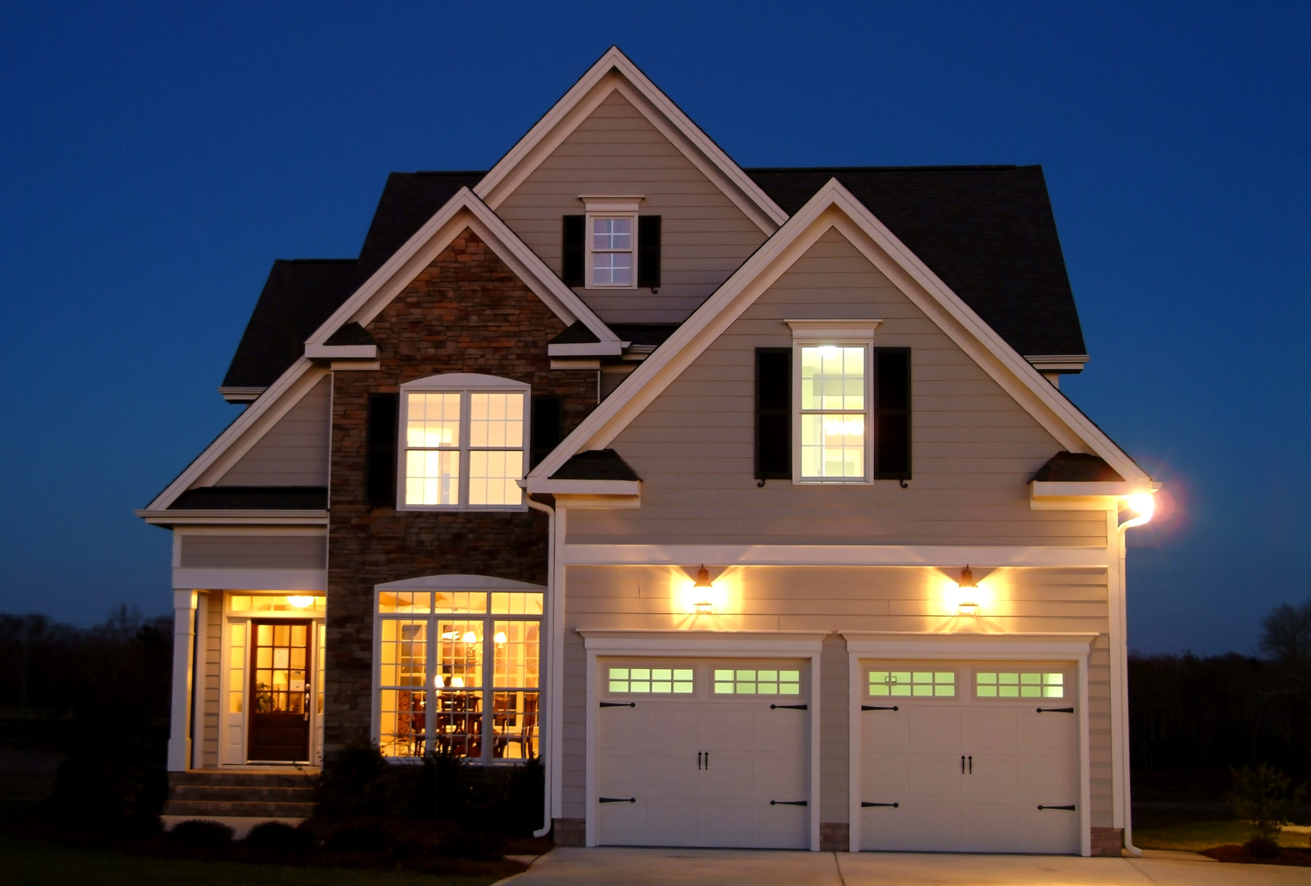 Two story home with two car garage in front of home - lights on at night