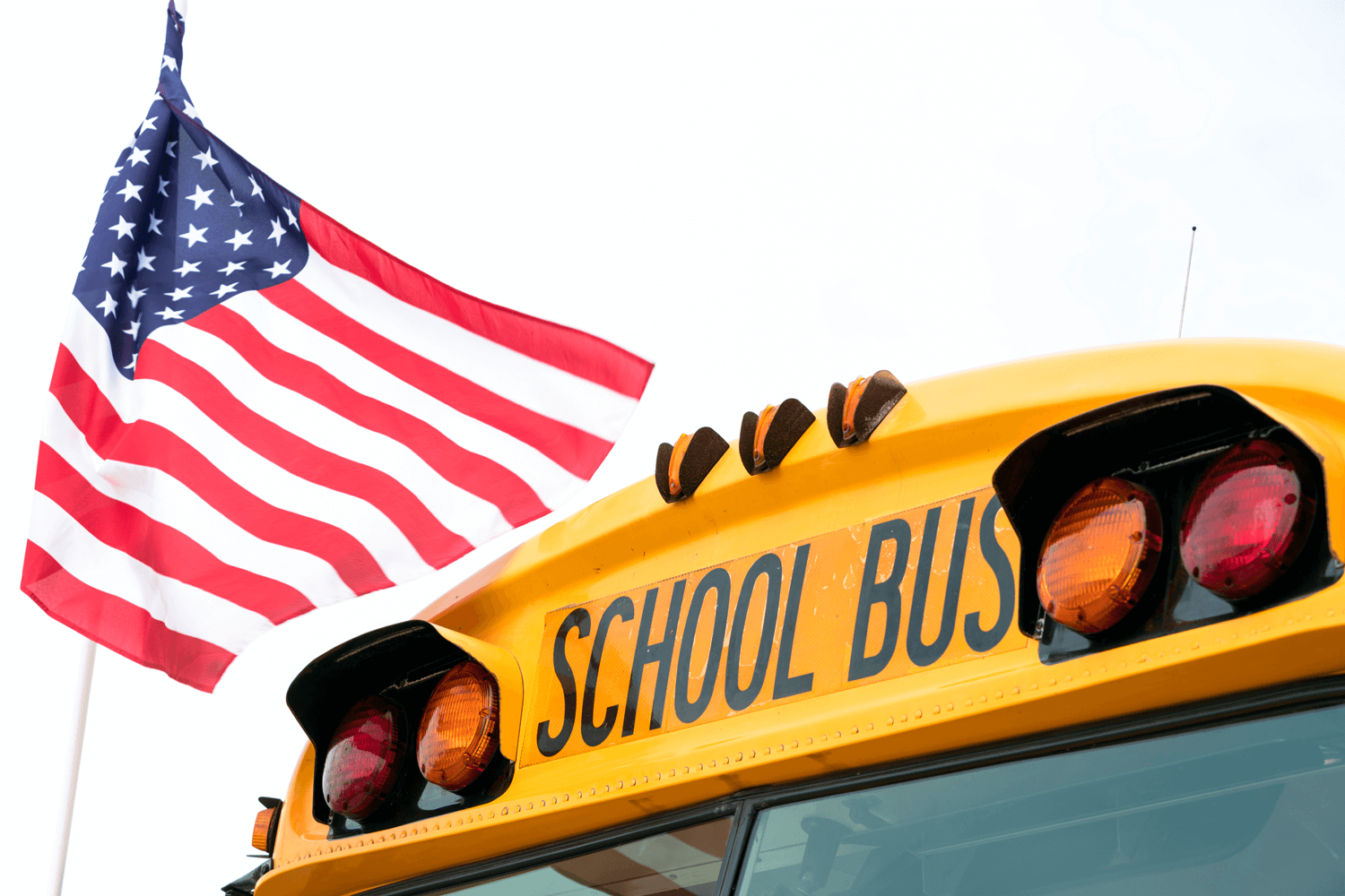 Close up of the top of a school bus with an American flag in the background
