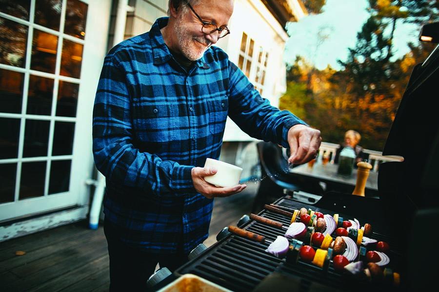 Guy seasoning skewers on gas grill